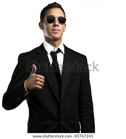 portrait of young business man with sunglasses with thumb up against a yellow background