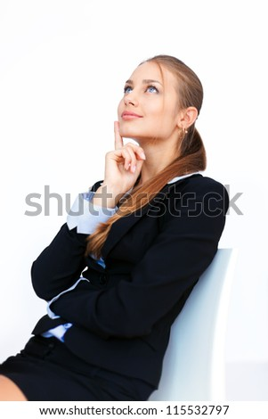Portrait of young business woman sitting on a chair and looking up