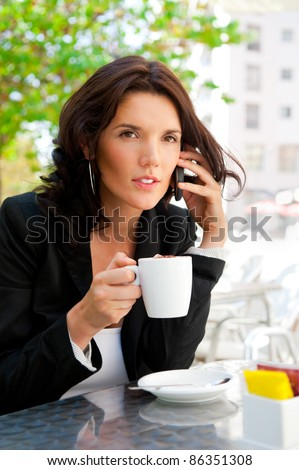 Portrait of young business woman sitting relaxed at outdoor cafe drinking coffee and chatting using her cell phone