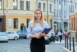 Portrait of young business woman with business papers, file folder, female looking at camera outdoors, city street background