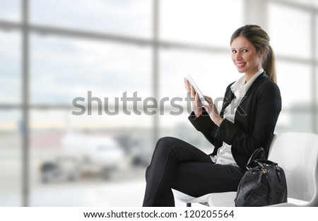 Portrait of young business woman working on digital tablet at airport