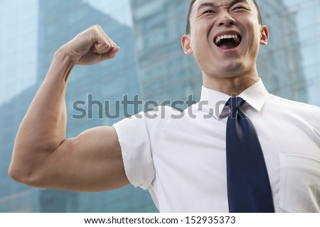 Portrait of young businessman flexing muscle outdoors