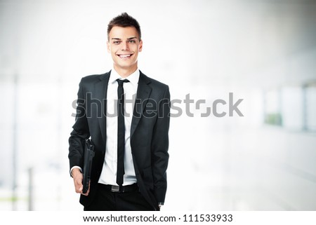 Portrait of young businessman holding laptop smiling.