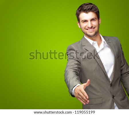 Portrait Of Young Businessman In A Suit Holds Out His Hand For A Handshake On Green Background