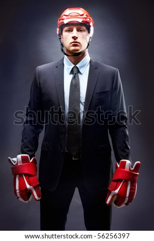 Portrait of young businessman in suit and hockey helmet and gloves