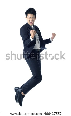 Portrait of young businessman jumping in the air and celebrating his success - Shutterstock ID 466437557