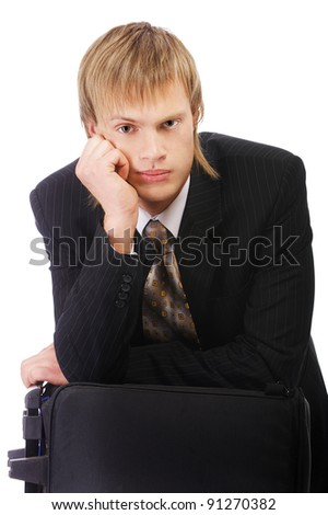 portrait of young businessman leaning his elbow on his travel bag