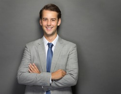 portrait of young businessman smiling with folded arms isolated on grey