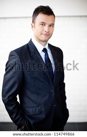 Portrait of young businessman standing agains the wall