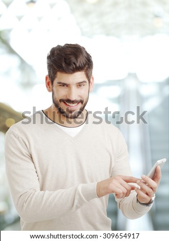 Portrait of young businessman standing at office and holding hands handy while typing text.
