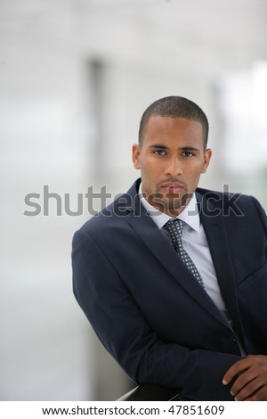 Portrait of young businessman standing in hall
