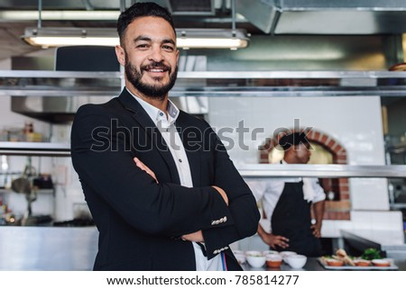 Portrait of young businessman standing in his restaurant with staff in kitchen. Proud restaurant owner standing with his arms crossed and looking at camera. #785814277
