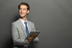 portrait of young businessman thinking while holding a tablet isolated on grey background with copy space