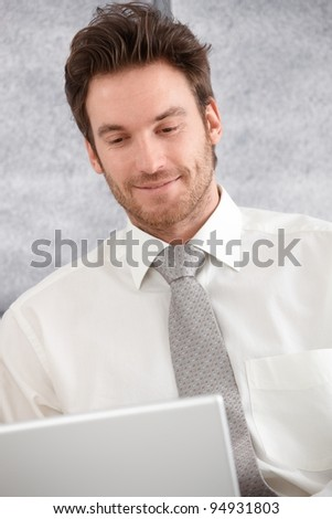 Portrait of young businessman using laptop, looking at screen, smiling.?