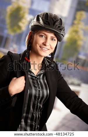 Portrait of young businessman wearing bike helmet, going to work, smiling.
