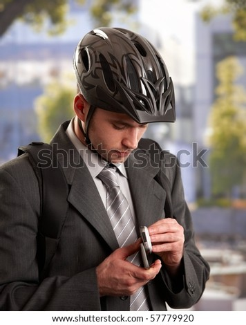 Portrait of young businessman wearing bike helmet, using mobile phone, outdoors.?