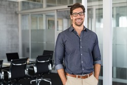 Portrait of young businessman wearing eyeglasses and standing outside conference room. Portrait of happy business man wearing spectacles and looking at camera with copy space. Satisfied proud man.