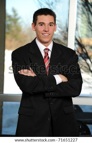 Portrait of young businessman with arms crossed indoors