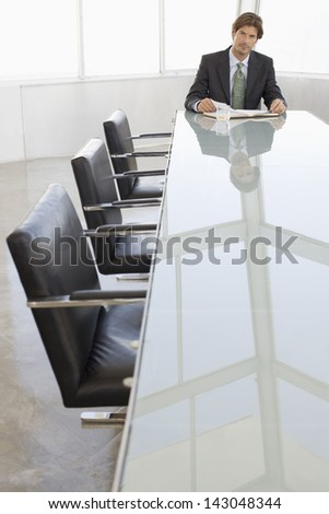 Portrait of young businessman with book at conference table
