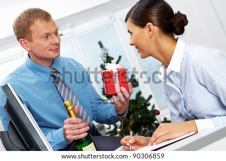 Portrait of young businessman with bottle of champagne giving present to his colleague