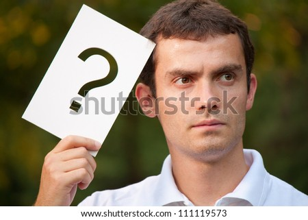 Portrait of young businessman with question mark