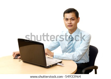 Portrait of young businessman working on laptop computer
