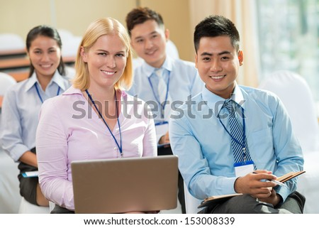 Portrait of young businesspeople with a laptop smiling and looking at camera in the foreground