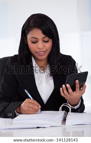 Portrait Of Young Businesswoman Doing Calculations In The Office