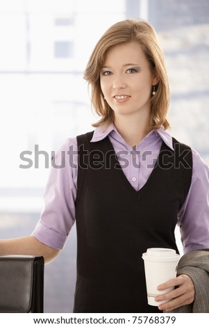 Portrait of young businesswoman holding coffee to go, smiling.