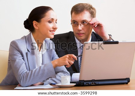Portrait of young businesswoman showing to the monitor of laptop and businessman touching his eyeglasses staring at her