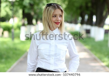 Portrait of young businesswoman standing in sunny park