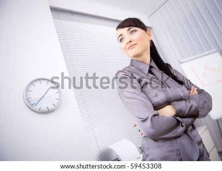 Portrait of young businesswoman standing with arms crossed in office, looking left. Low-angle shot.