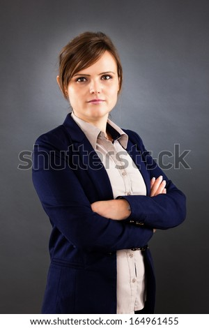 Portrait of  young businesswoman standing with arms folded over white background