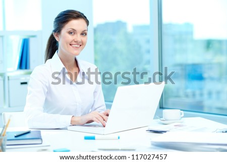 Portrait of young businesswoman typing on laptop