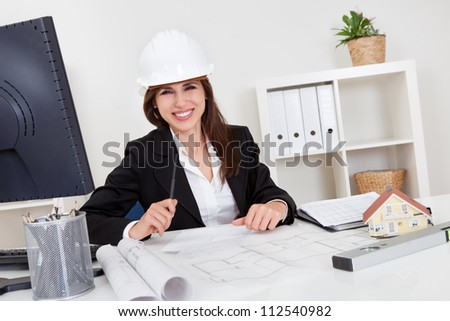 Portrait of young businesswoman wearing hardhat with blueprints at office desk