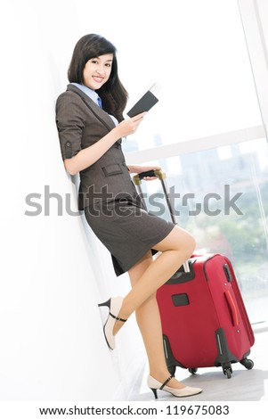 Portrait of young businesswoman with baggage looking at camera in airport