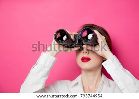 Portrait of young  businesswoman with binoculars on pink background. Concept of looking for new job