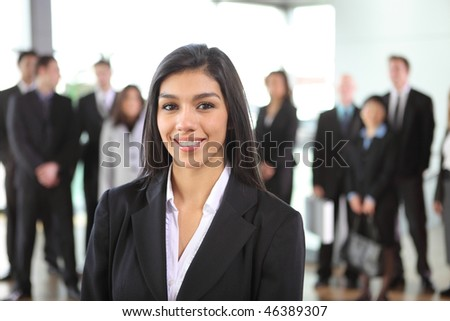Portrait of young businesswoman with people in background