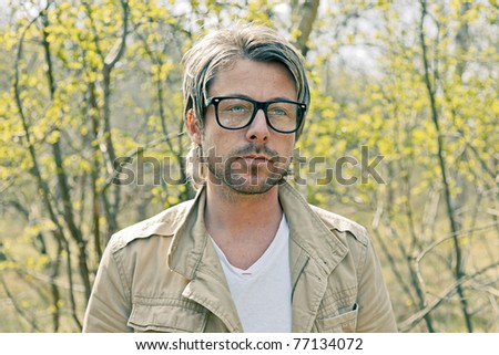 Portrait of young casual man with glasses standing in nature.