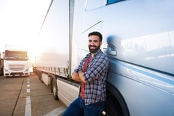 Portrait of young Caucasian bearded trucker with arms crossed standing by his truck vehicle. Transportation service. Truck driver job.