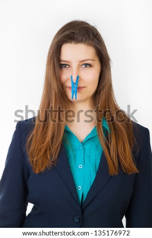 Portrait of young caucasian business woman with Clothespin on her nose - bad smell concept