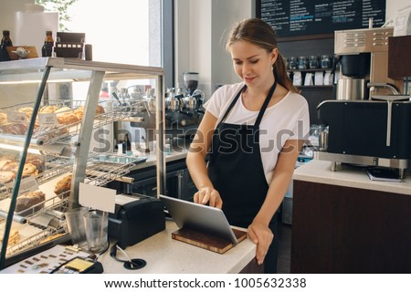 Portrait of young caucasian female woman cashier. Seller using touch pad for accepting client customer payment. Small business of coffee shop cafeteria.