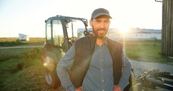 Portrait of young Caucasian handsome happy man farmer standing in field and smiling to camera. Big tractor on background. Cheerful male worker in agricultural farm. Sunlight. Agriculture farming.