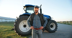 Portrait of young Caucasian handsome man farmer in cap standing on the road in field and smiling to camera. Big tractor on background. Male worker in agricultural farm. Agriculture farming.