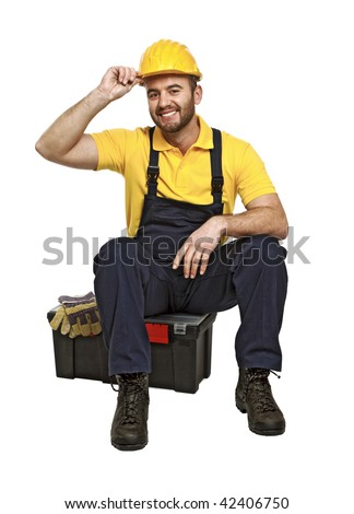portrait of young caucasian handyman sit on his toolbox on white background