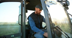 Portrait of young Caucasian male farmer in cap sitting in tractor with open door and smiling to camera. Field farming vehicle. Machine for agriculture. Handsome smiled man.