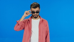 Portrait of young caucasian man in his 20s on blue background in studio. Beautiful handsome man wearing sunglasses. Being disturbed by the sun. Blue background.