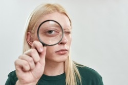 Portrait of young caucasian man with long blond hair holding magnifying glass near enlarged eye on light background. Male beauty concept
