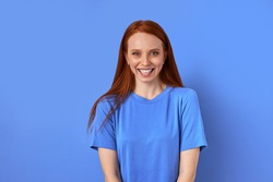 portrait of young caucasian redhead female with perfect freckled skin, smiling at camera. positive female has beautiful toothy smile. isolated blue background