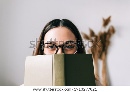 Portrait of young caucasian woman college student in eyeglasses hiding behind a book and looking at camera. Foto stock ©